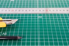 Cutter, ruller and pencil on a green cutting mat stock photo
