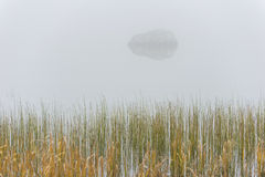 Cutthroat Lake in the fog. A small lake in the North Cascade Mountain range is surrounded by fog on this autumn day in October giving it a spooky feel. A rock royalty free stock images