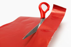 Cutting. A red wrapping paper with a pair of red scissors Stock Images