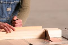 Cutting. A female woodworker cross cuts apiece of pine Royalty Free Stock Photos
