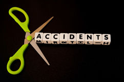 Cutting accidents. Text ' accidents ' in black uppercase letters on small white cubes with pair of scissors symbolizing cutting, dark background Royalty Free Stock Photo