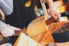 Cutting aged cheese in grocery shop. Cutting aged cheese, parmesan cheese in grocery shop, closeup stock image