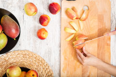Cutting apple while getting online information about nutrition Stock Photos