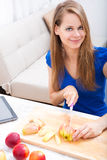 Cutting apple while getting online information about nutrition Royalty Free Stock Photography