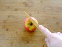 Cutting an Apple. Man is cutting an Apple with a Kitchen Knife on wooden Cutting Board Stock Image