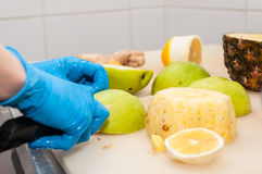 Cutting apple. And pineapple on juice factory stock photography