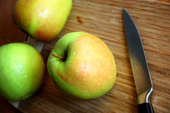 Cutting apples. Three apples and knife on a wooden table Royalty Free Stock Photos