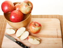 Cutting Apples on Wood Cutting Board. Apples in a wood bowl and on cutting board with some cut in half Royalty Free Stock Photography