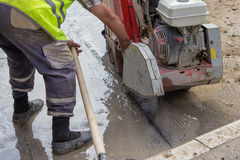 Cutting asphalt road with diamond saw blade Stock Images