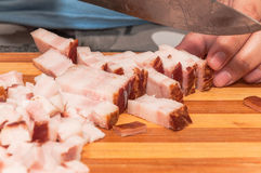 Cutting bacon filleted with a steel knife. On a cutting board Stock Image
