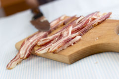 Cutting bacon into strips, close up Royalty Free Stock Photos