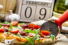 Cutting baked pizza in the background with calendar Stock Photos