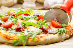 Cutting baked pizza with tomatoes and ham Stock Images