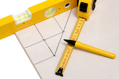 Cutting bathroom tiles. Measuring tape and pen on bathroom tile with cutting lines sketched stock photography