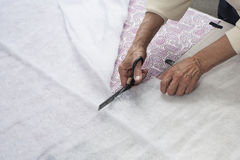 Cutting batting. A quilter cutting batting to layer and sandwich a quilt Stock Image