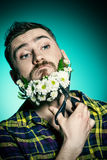Cutting beard. Funny and handsome young man cut his beard of flowers with scissors Stock Photos