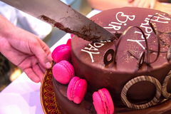 Cutting the beautifully decorated  a festive chocolate cake with the inscription Happy Birthday Stock Images