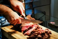 Cutting beef meat slices. Male chef hands with knife cutting slices of beef meat Stock Photos