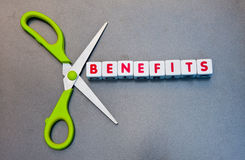 Cutting benefits. Scissors set against text ' benefits ' in uppercase red letters inscribed on small white cubes, relating to welfare bill, gray background stock image