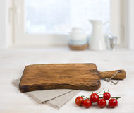 Cutting board above linen tablecloth on wooden table. Cooking concept.  Stock Photo