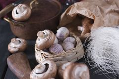 Cutting board and basket with different kinds of mushrooms on wooden background. Cutting board and basket with different kinds of mushrooms on wooden background royalty free stock photography