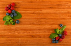 Cutting board with blueberries, raspberries and mint leaves in c. Taste of summer - cutting board with mellow blueberries, raspberries and mint leaves in corners Stock Image