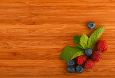 Cutting board with blueberries, raspberries and mint leaves. Taste of summe, cutting board with mellow blueberries, raspberries and mint leaves Stock Photography