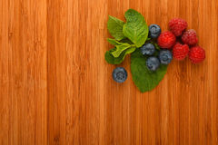 Cutting board with blueberries, raspberries and mint leaves. Taste of summer - cutting board with mellow blueberries, raspberries and mint leaves – add your Royalty Free Stock Photography
