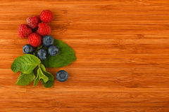 Cutting board with blueberries, raspberries and mint leaves. Taste of summer - cutting board with mellow blueberries, raspberries and mint leaves – add your Royalty Free Stock Photo