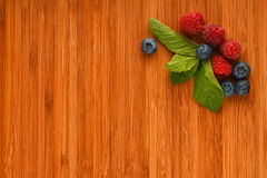 Cutting board with blueberries, raspberries and mint leaves. Taste of summer - cutting board with mellow blueberries, raspberries and mint leaves – add your Royalty Free Stock Images
