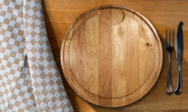 Cutting Board and Cutlery - Table and Tablecloth. Empty round cutting board on a wooden table with silver cutlery, fork and knife, and a brown and white Royalty Free Stock Photography