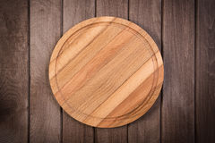 Cutting board on dark wooden background Stock Images
