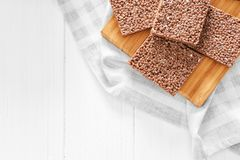 Cutting board with delicious chocolate rice treats. On light table Stock Images