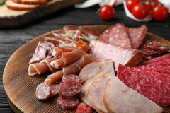 Cutting board with different sliced meat products served. On table royalty free stock images