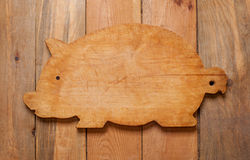 Cutting board in the form of a pig on an old wooden table01 Royalty Free Stock Photography