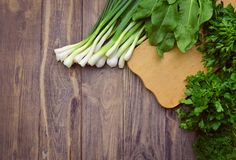 Cutting board and frame from fresh greens. board background. Fla. Healthy food background. Fresh spinach, dill, parsley, sorrel, green onions, rustic cutting royalty free stock image