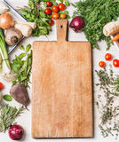 Cutting board and fresh organic vegetables for tasty vegan or vegetarian cooking, top view, frame Royalty Free Stock Photos