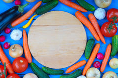 Cutting board among fresh vegetables Stock Images