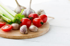 Cutting board with fresh vegetables on white wooden table. Copyspace Stock Photos