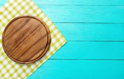 Cutting board and green plaid tablecloth on blue wooden background. Top view and copy space. Place for text. Mock up Royalty Free Stock Photos