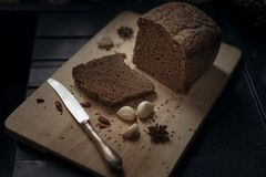 Dark bread, garlic and knife on a cutting board royalty free stock images