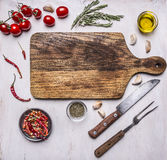 Cutting board with herbs, a knife and fork, cherry tomatoes, butter and herbs around it place for text on white wooden rustic back Royalty Free Stock Photos