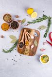 Cutting board with herbs and spices  - rosemary, garlic, salt, pepper, olive oil, lemon. Culinary background. Food flat lay Stock Image