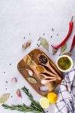 Cutting board with herbs and spices  - rosemary, garlic, salt, pepper, olive oil, lemon. Culinary background. Food flat lay Stock Photo