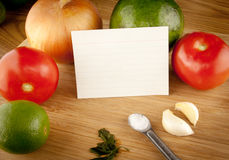 Cutting Board With Ingredients And Blank Recipe Card. Ingredients sitting on top of a cutting board with a blank white recipe card Stock Image