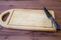 Cutting board with a kitchen knife on atable. Cutting board with a kitchen knife on a wooden table Royalty Free Stock Images