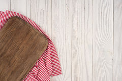 Cutting board on a kitchen napkin on old wooden table. Stock Image