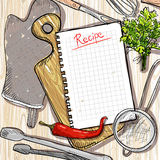 Cutting board and kitchen utensil with empty recipe list on a wooden table Royalty Free Stock Images