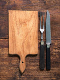Cutting board, knife and fork Stock Photos