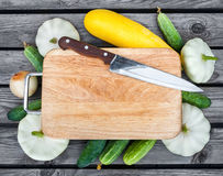 Cutting board, knife, fresh vegetables on wooden table.  Top vie Stock Photography